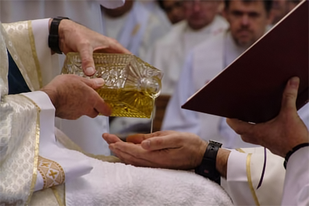 Anointing of hands during the sacrament of ordination.